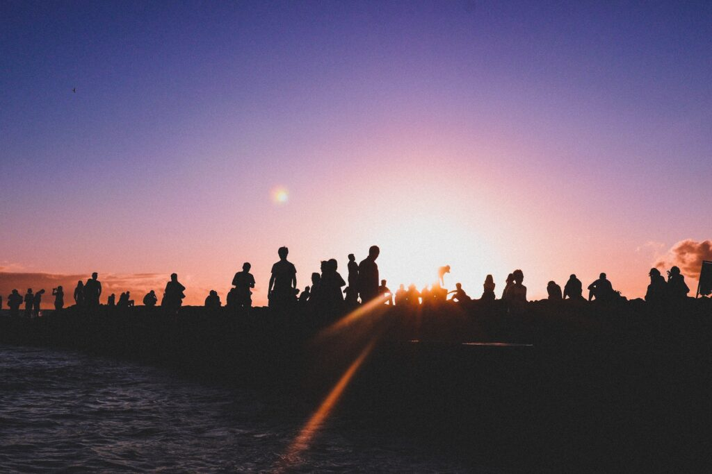 People gathered at sunset. Narrative organizing. Photo by Rita Vicari, Unsplash.
